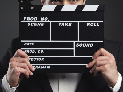 Business man holding a clapboard